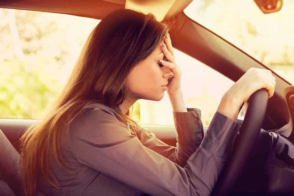 chica joven sufriendo problemas de estrés mientras conduce su coche